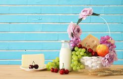 Image of fruits and cheese in decorative basket with flowers over wooden table. Symbols of jewish holiday - Shavuot. Stock Photography