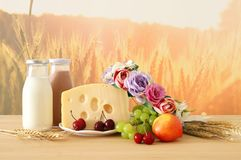 Image of fruits and cheese in decorative basket with flowers over wooden table. Symbols of jewish holiday - Shavuot. Royalty Free Stock Photography