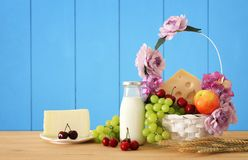 Image of fruits and cheese in decorative basket with flowers over wooden table. Symbols of jewish holiday - Shavuot. Stock Photo