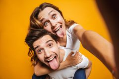 Image of funny couple having fun and taking selfie with tongues. Out while men piggybacking caucasian women isolated over yellow background stock photos
