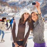 Image of funny teenagers girls taking selfie, ice rink outdoor Royalty Free Stock Photo