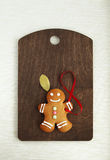 Image of Gingerbread man on brown cutting board Royalty Free Stock Photography