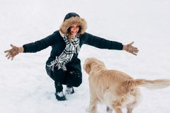 Image of girl hugging labrador in winter park for walk. At afternoon Royalty Free Stock Photo