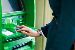 Image of girl picking pincode at green cash dispenser. In room Royalty Free Stock Images