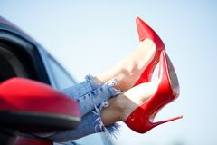 Image of girl`s legs in red shoes sticking out of red car window stock photos