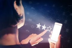 User feedback, quality assessment, product and service ratings. Image of a girl with a smartphone in hands. She presses on the three stars rating icon. User Stock Images