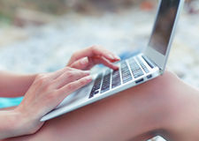 Image of girls hands typing on the beach. Selective focus Stock Image