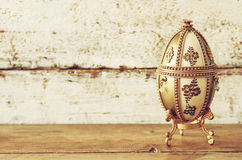 Image of gold faberge egg on wooden table Royalty Free Stock Photography