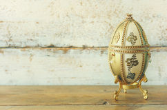 Image of gold faberge egg on wooden table Royalty Free Stock Photos