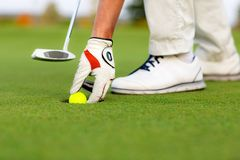 Male hand is putting out a ball from golf hole royalty free stock photos