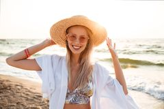 Image of gorgeous blonde woman 20s in summer straw hat and sungl. Asses smiling while walking at sea coast Royalty Free Stock Image