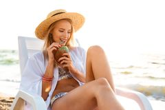 Image of gorgeous caucasian woman 20s in straw hat drinking swee Royalty Free Stock Photos