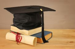 Image of graduation black hat over old books next to graduation on wooden desk. Education and back to school concept. royalty free stock photos