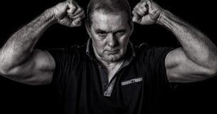 Image graveleuse d'un type non rasé posant avec les poings serrés et son le biceps fléchis image stock