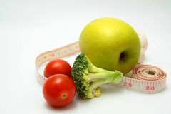 Apple with tape measure sitting n table Royalty Free Stock Photo