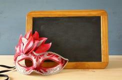 Image of green elegant venetian mask. Next to empty blackboard Royalty Free Stock Photos