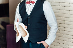 Image of a groom holding bridal shoes Stock Photography