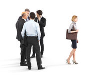 Image of a group of businessmen standing with a businesswoman walking in front. Royalty Free Stock Photography