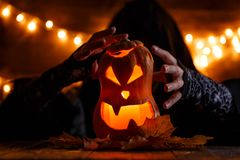 Image of halloween pumpkin cut in shape of face with witch. On background with burning yellow lights Stock Images