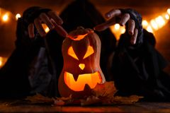 Image of halloween pumpkin cut in shape of face with witch. On background with burning yellow lights Stock Image