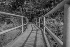 Image of a handrail of a metal bridge ending in a forest. Between Elsloo and Meers South-Limburg in the Netherlands, copy space or space for text royalty free stock images