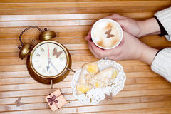 Image of hands holding cup of hot drink with pastries on plate, small gift box and alarm clock around Royalty Free Stock Photography