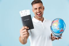 Handsome excited happy adult man posing isolated over blue wall background holding passport with tickets and globe royalty free stock photography