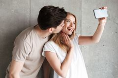 Image of handsome man kissing pretty woman on cheek and taking s. Image of handsome men kissing pretty women on cheek and taking selfie photo on smartphone over stock photography