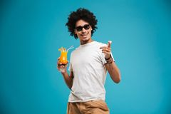Handsome young african curly man holding cocktail pointing. Image of handsome young african curly man standing isolated over blue background holding cocktail Stock Photos