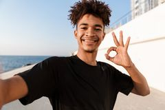 Young guy sportsman standing outdoors on the beach make selfie by camera showing okay gesture stock photography