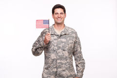 Image of a handsome young soldier posing with an American flag Stock Photography