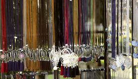 The image of hanging women`s jewelry on colored laces in the store. Fashionable jewelry on the neck for women. stock photos