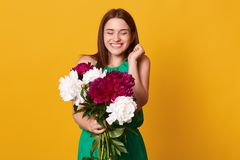 Image of happy brunette girl, stands with smiling and holding bouquet of white and burgundy peonies, expresses happyness and. Gladness, has gift for holiday stock image