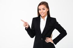 Happy business woman pointing to copyspace. Image of happy business woman standing isolated over white background. Looking camera pointing to copyspace Stock Image