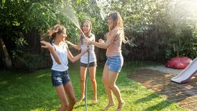 Photo of happy cheerful girls in wet clothes dancing and jumping under water garden hose. Family playing and having fun. Image of happy cheerful girls in wet stock photography