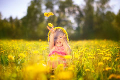 Image of happy child on dandelions field, cheerful little girl r Royalty Free Stock Photos