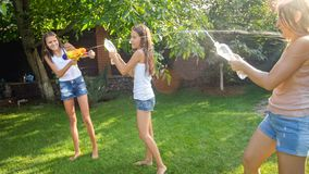 Image of happy children playing in the house backyard garden with water guns and garden hose. Family playing and having. Photo of happy children playing in the stock photography