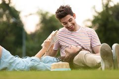 Image of man and woman 20s lying on green grass in park and reading book royalty free stock images
