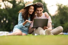 Image of man and woman sitting on grass in park and using laptop stock photo