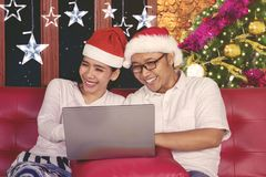 Happy couple using a laptop at Christmas time Royalty Free Stock Photography