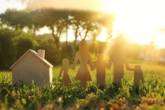 Image of happy family concept. wooden cut people holding hands together next to home in green grass during sunset. Image of happy family concept. wooden cut stock images