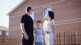 Image of happy family dressed in casual clothes standing near their new house in sunny summer day. Father, mother and stock video footage