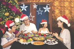 Happy family enjoying dinner at Christmas time. Image of happy family enjoying dinner together while celebrating Christmas at home Stock Photos