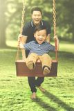 Happy father and his son playing with swing. Image of Happy father and his son playing with a swing while having fun together in the park Stock Photo