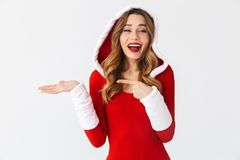 Image of happy girl 20s wearing Christmas red dress pointing holding copyspace at palm while standing, isolated over white stock photo