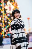 Image of happy girl on street , blurred background with burning garland stock photography