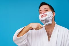 Image of happy man in white coat shaving. On empty blue background royalty free stock photography