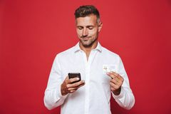 Image of happy man in white shirt holding credit card and smartp royalty free stock images