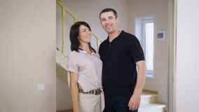 Image of happy man and woman in living room standing near window and embracing each other. Loving couple moving into new stock video