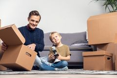 Image of happy man and small boy with microscope sitting on floor among cardboard boxes stock photos